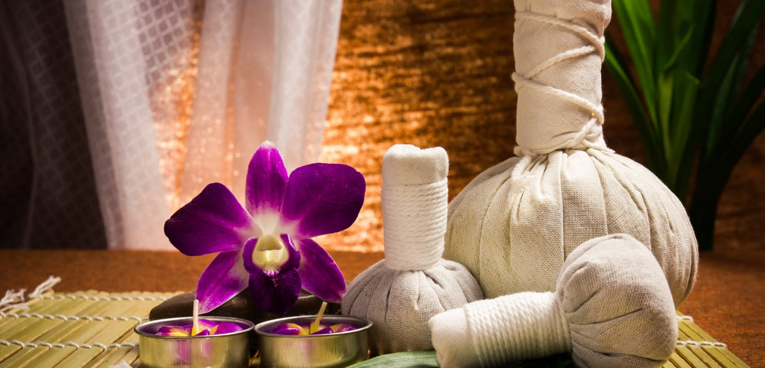 Spa herbal compressing ball with candles and orchid on brown background.