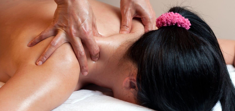 Thai massage therapists doing a neck massage for a female client.