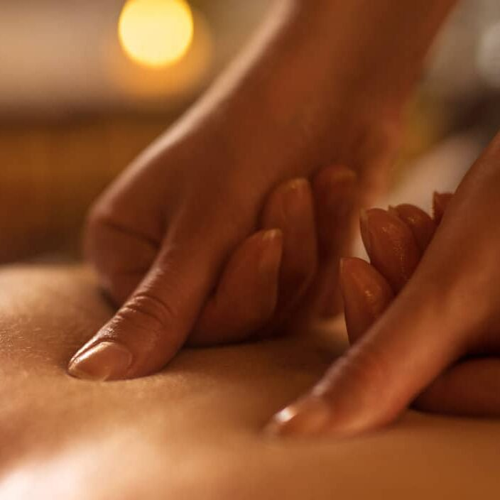 Close-up of massage therapist applying pressure on man's back at the spa.