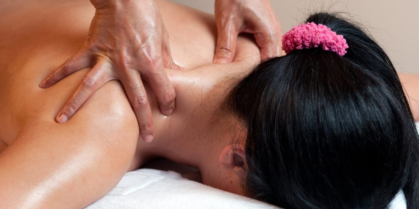Thai massage therapists doing a neck massage for a female client.