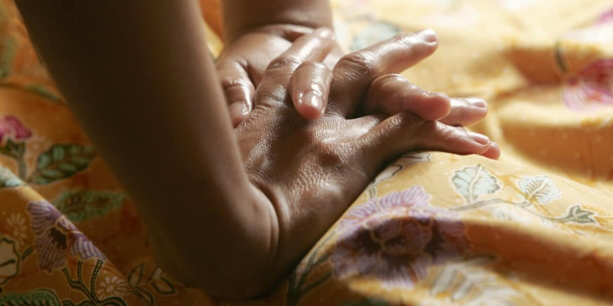 Hands massaging. You can not see the woman gets massage when she is under a dress